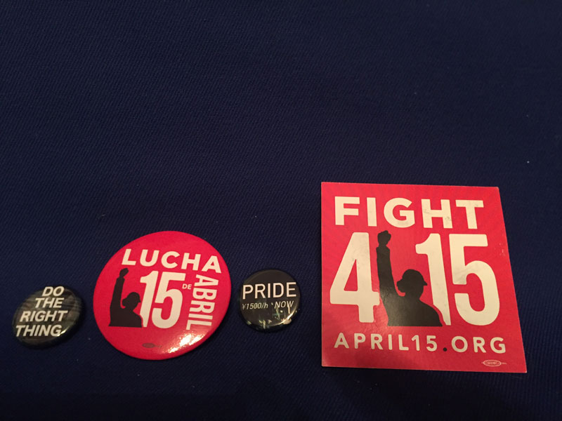 Stickers and badges calling for an increase in the minimum wage.