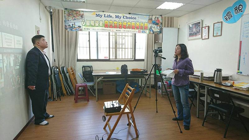 台湾代表者である曾さんと私の録画風景。彼がカメラの前で話し、私は後ろで通訳した。(新竹市智障福利協進会提供)